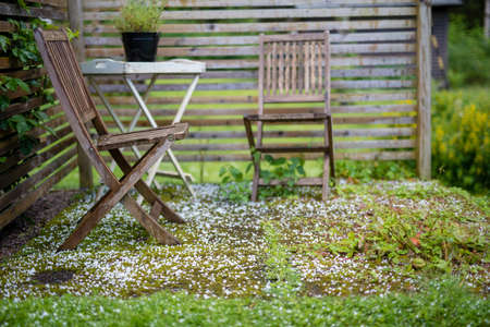 too chairs standing outside after a hail storm