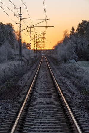 straight rail road tracks into a beautiful orange sunset Banco de Imagens