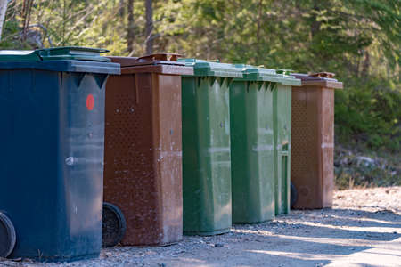 Trash cans standing beside a gravel road