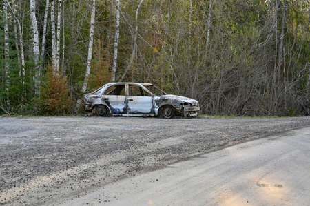 a burnt down car at a gravel road Reklamní fotografie