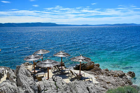 empty stone beach with sunshades in Rabac Croatia