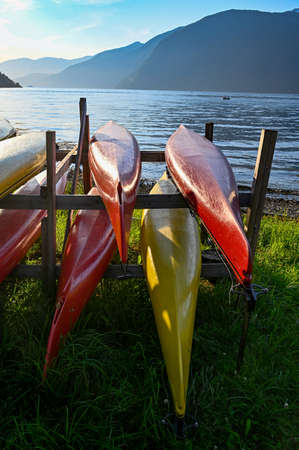 eight kayaks in yellow and red on a rack