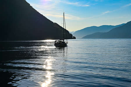 sailing boat late a summers evening on a fjord i Norway Stockfoto