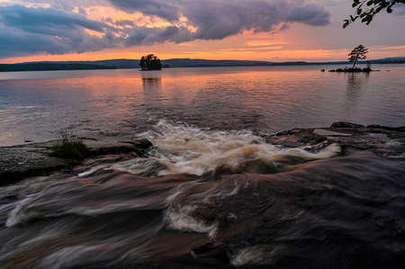 streaming water and colorful sunset over lake