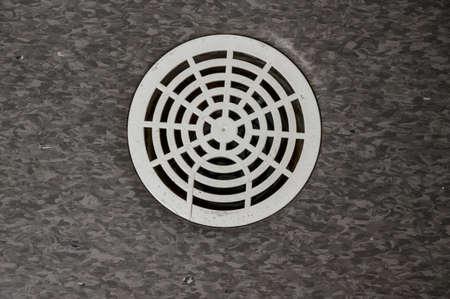 draining gutter in floor on public toilet