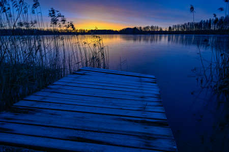 sunrise over wooden jetty and frozen lake