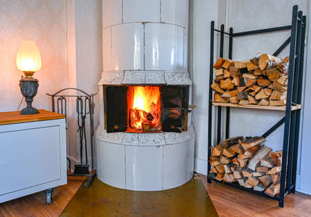 fire in a tiled stove in a cabin