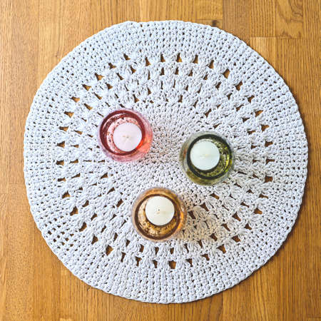three candles on a crocheted table cloth
