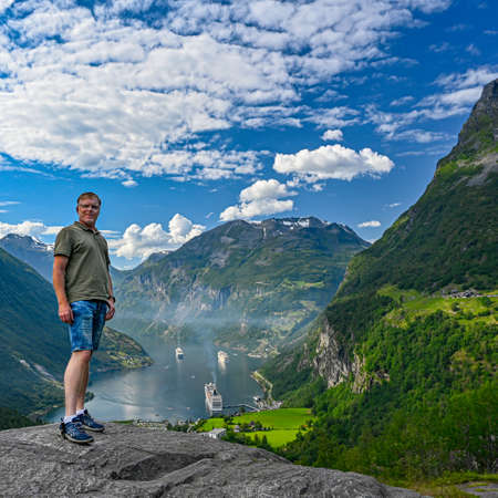 Male tourist standing high near Giranger in Norway