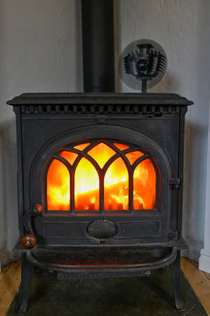 cast iron stove with small fan on top