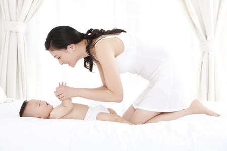 arrodillarse: Madre china y adorable bebé en casa