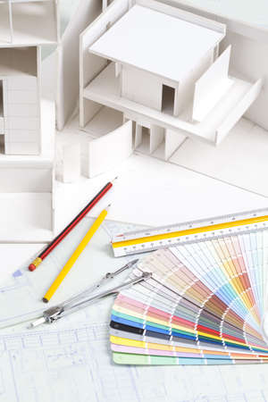 architect tools: Architectural model with other office stationery on blueprints
