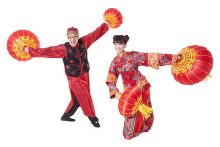 Cheerful young couple in Tang suit dancing with Chinese lantern in hands