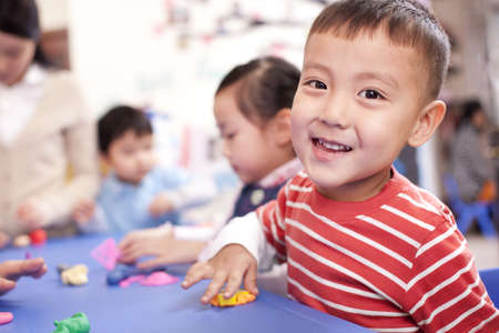 child's play clay: Lovely children playing with plasticine in kindergarten