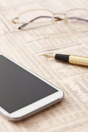 Financial newspaper and mobile phone on desk