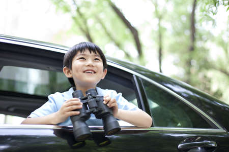 transportation: Cheerful boy leaning out of car window with binoculars in hands LANG_EVOIMAGES