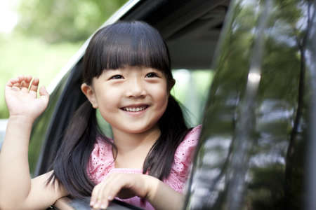 Cheerful girl waving out of car window LANG_EVOIMAGES