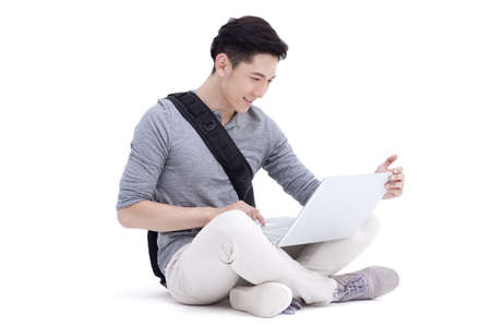 Happy male college student using laptop