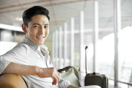 Young man waiting in airport lounge LANG_EVOIMAGES