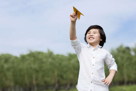 Happy boy playing paper airplane in the open air