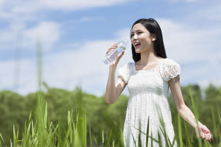 purified: Young woman drinking water outdoors