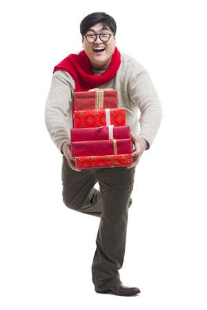 lipid: Cheerful young man with Chinese New Years gifts LANG_EVOIMAGES