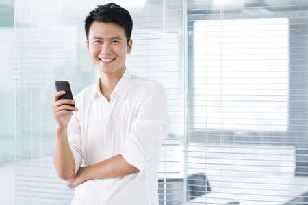 Young man with mobile phone in office