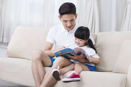Father and daughter reading a book on the sofa