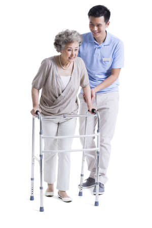 Male nursing assistant helping senior woman with walking frame LANG_EVOIMAGES