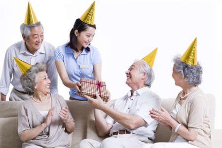 Female nursing worker and senior adults enjoying birthday party LANG_EVOIMAGES