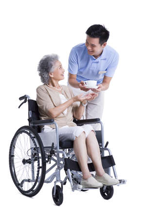 Male nursing assistant handing wheelchair bound woman a cup of coffee