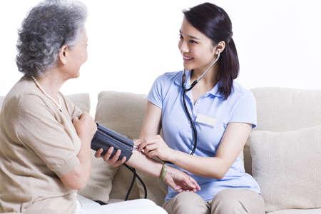 Nursing assistant taking senior womans blood pressure