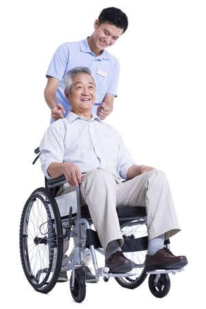 Male nursing worker helping senior man doing massage on the back