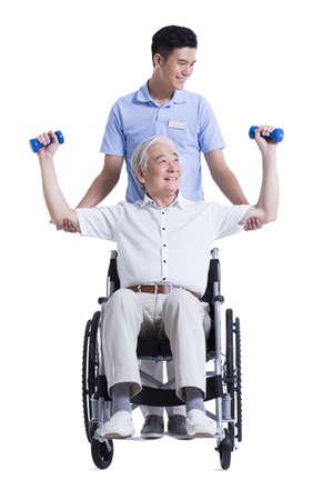 Male nursing worker helping senior man doing exercise