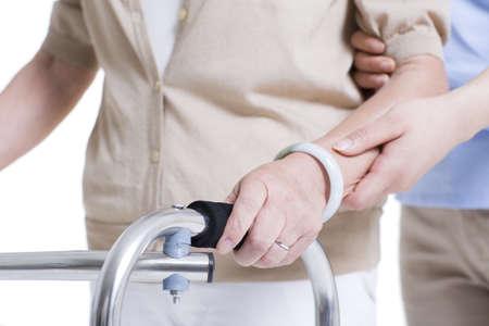 Nursing assistant helping senior woman with walking frame LANG_EVOIMAGES