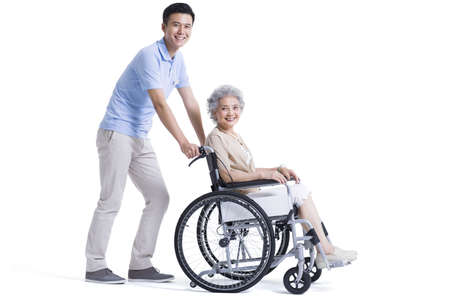 Male nursing assistant taking care of senior in wheelchair LANG_EVOIMAGES