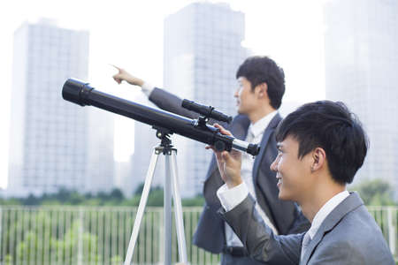 the bigger picture: Confident young businessmen with telescopic equipment