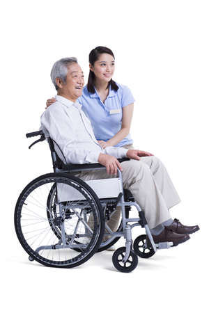 Female nursing assistant taking care of senior in wheelchair LANG_EVOIMAGES