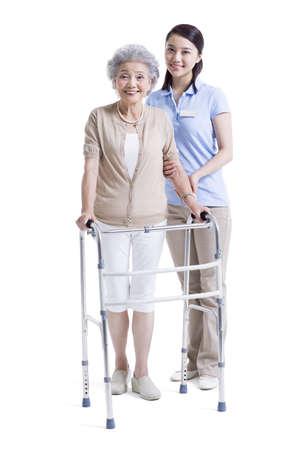 Female nursing assistant helping senior woman with walking frame LANG_EVOIMAGES