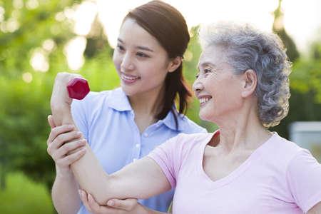 flexing: Senior woman exercising with dumbbell in nursing home