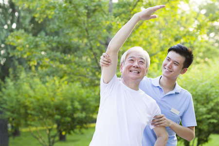 Senior man exercising with nursing assistants help