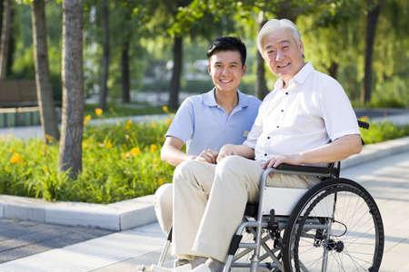 Wheelchair bound man with nursing assistant LANG_EVOIMAGES