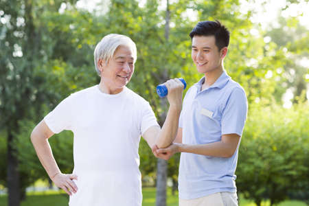 Senior man exercising with dumbbell in nursing home LANG_EVOIMAGES