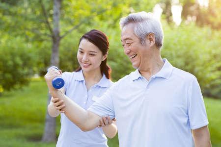 Senior man exercising with dumbbell in nursing home LANG_EVOIMAGES