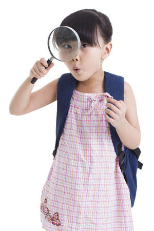 Cute little girl with magnifying glass LANG_EVOIMAGES