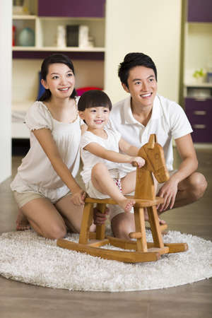 Young family playing wooden horse chair