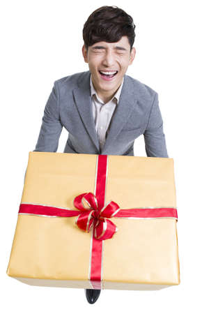 Young man laughing with a large gift LANG_EVOIMAGES