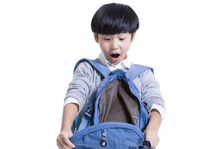 Cute schoolboy opening book bag with surprise LANG_EVOIMAGES