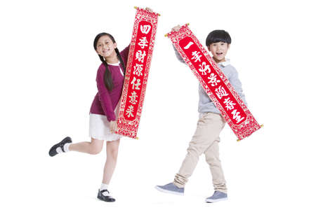Happy children with couplets celebrating Chinese New Year