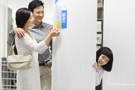 Girl hiding in wardrobe while parents checking the price tag